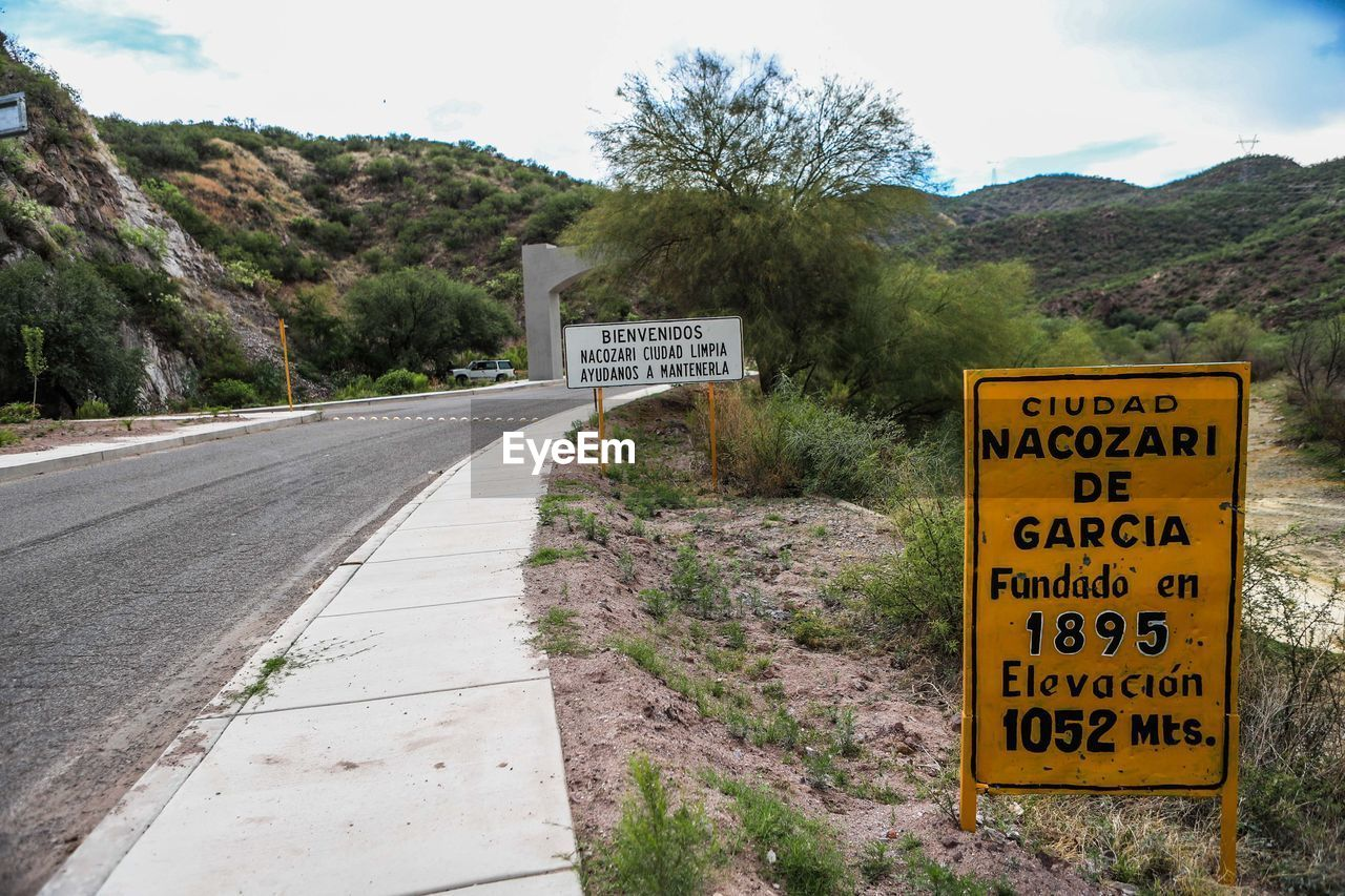text, western script, communication, mountain, day, warning sign, outdoors, no people, tree, road, nature, sky, plant, beauty in nature