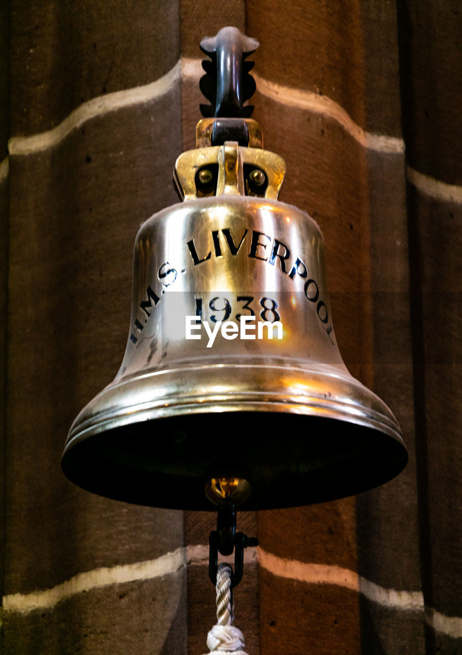 bell, metal, hanging, no people, indoors, communication, wall - building feature, close-up, text, focus on foreground, architecture, day, shiny, wall, built structure, gold colored, wood - material, number, still life, electric lamp