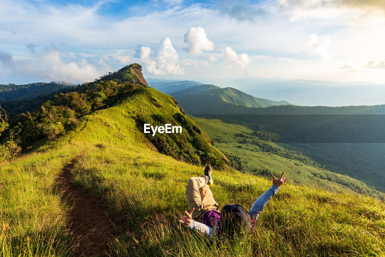 Man with arms raised lying on mountain against sky
