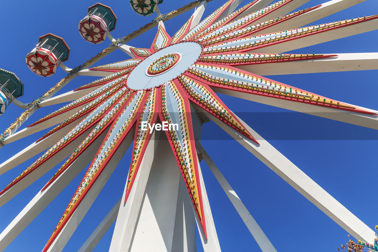 low angle view, amusement park ride, sky, amusement park, arts culture and entertainment, ferris wheel, no people, blue, clear sky, nature, metal, day, architecture, built structure, outdoors, tall - high, pattern, enjoyment, carnival, fun, fairground