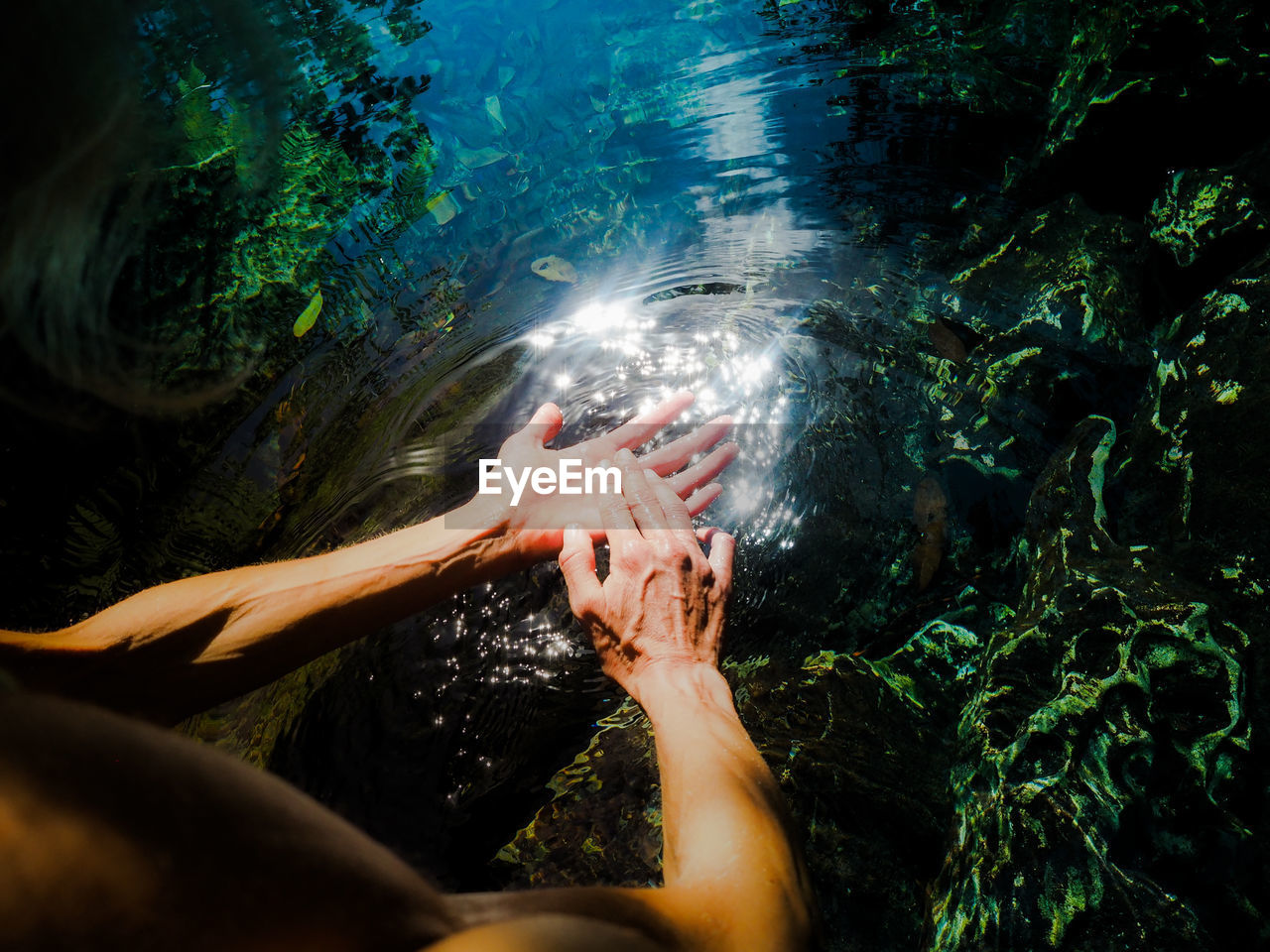 Cropped Image Of Woman Washing Hands In Lake