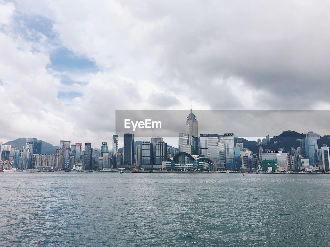 Hong kong skyline against cloudy sky
