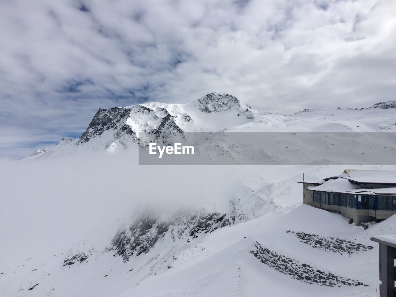 cold temperature, winter, snow, cloud - sky, sky, mountain, architecture, beauty in nature, scenics - nature, built structure, white color, environment, building exterior, landscape, nature, covering, building, tranquil scene, no people, snowcapped mountain, extreme weather, range