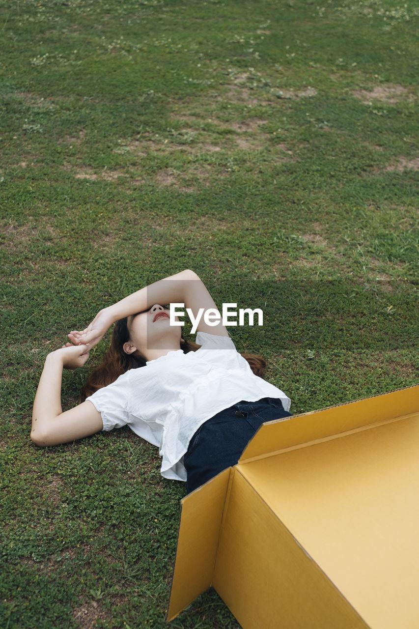 Woman lying on grass in cardboard box