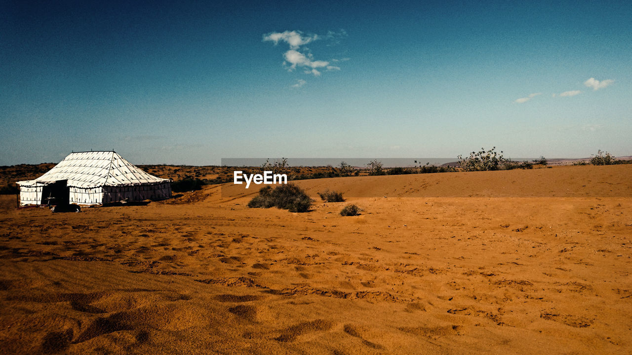 sky, land, architecture, built structure, nature, environment, landscape, building exterior, sand, scenics - nature, desert, tranquil scene, cloud - sky, blue, tranquility, no people, day, beauty in nature, sunlight, field, arid climate, outdoors, climate