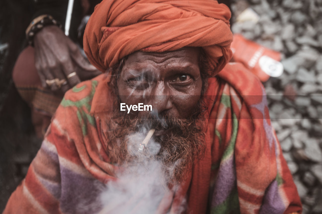 Close-up portrait of a man , smoking.