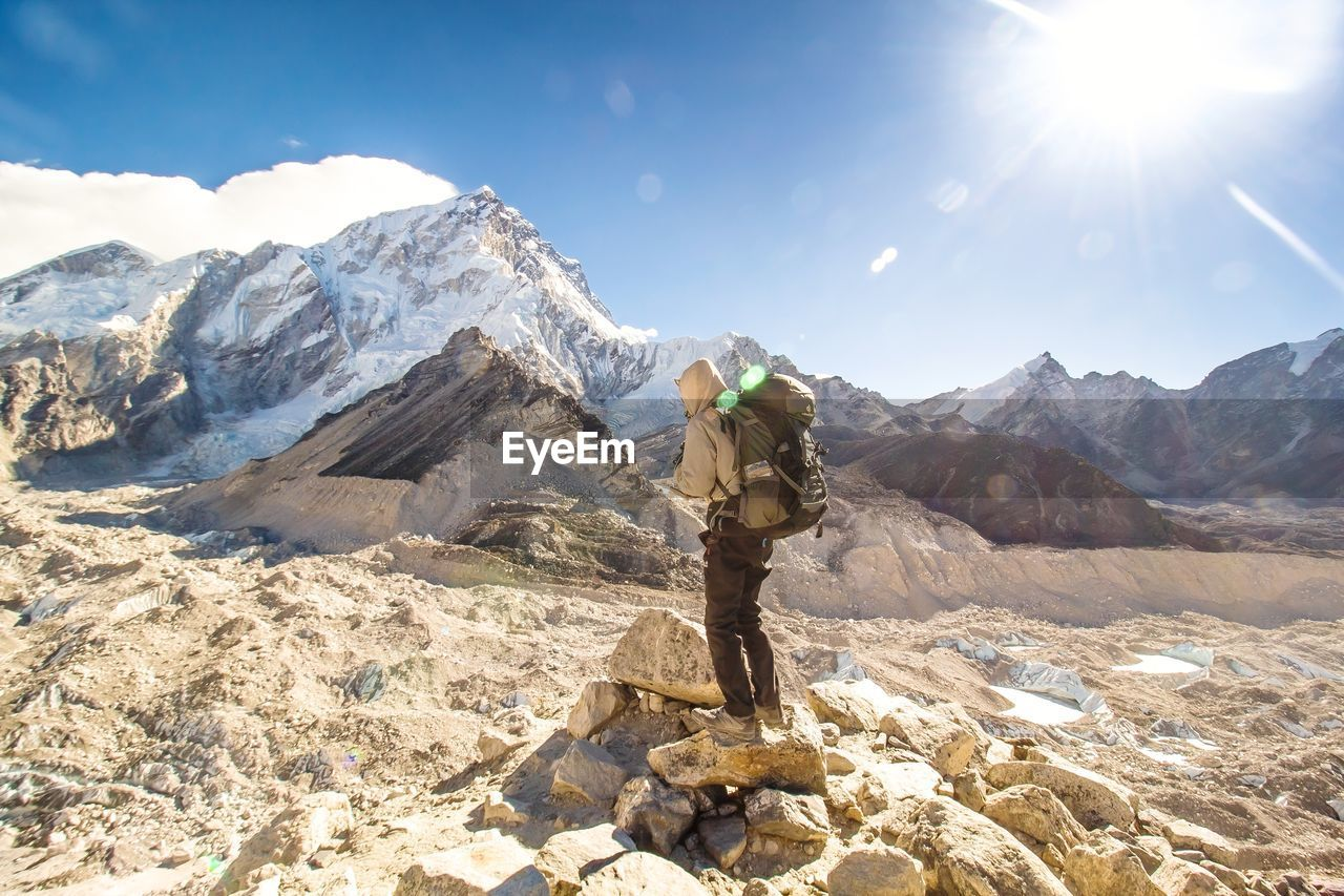 Side view of backpacker standing on rock by mountains against sky during sunny day
