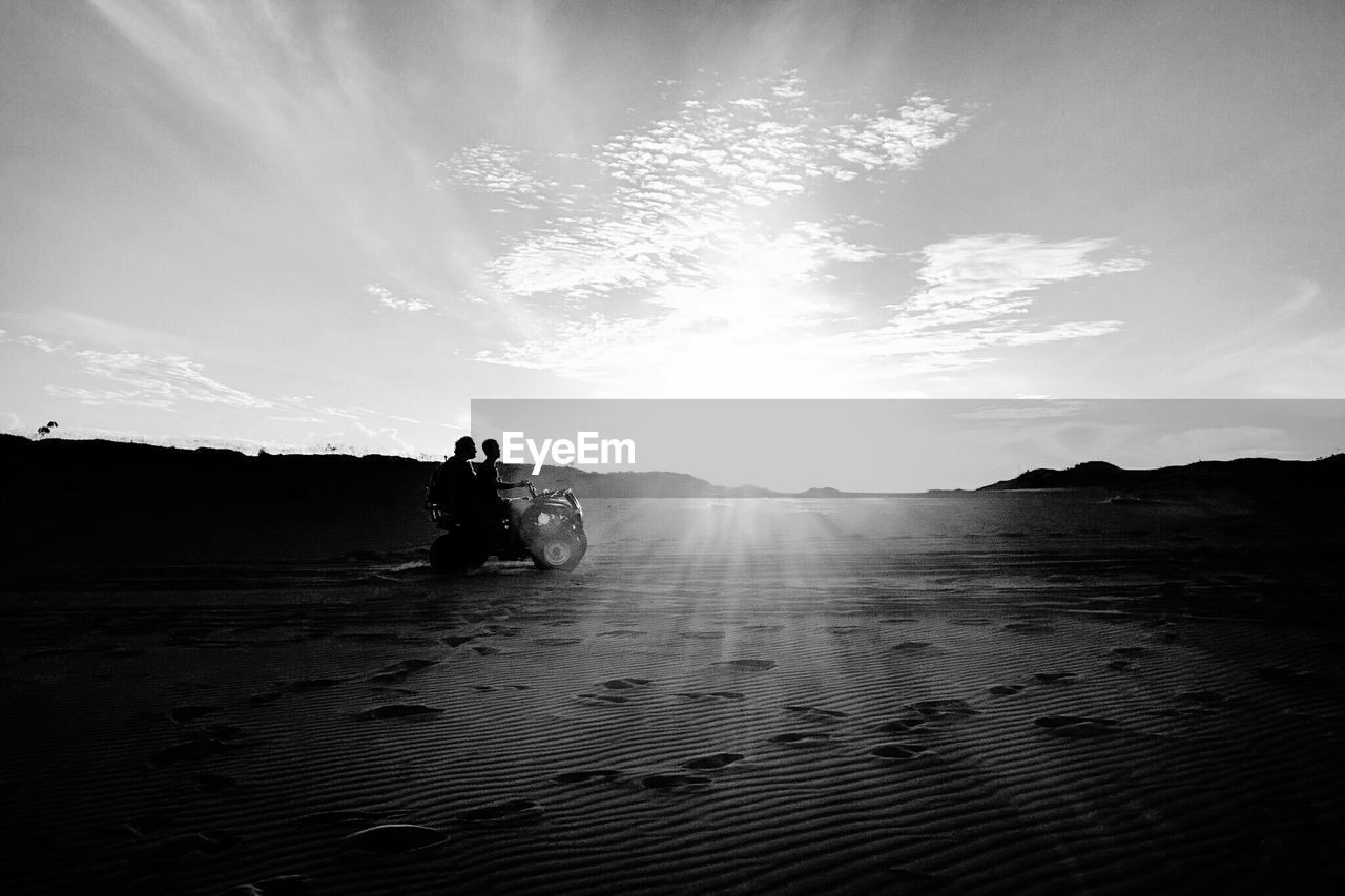 Friends Riding Quadbike On Field Against Sky