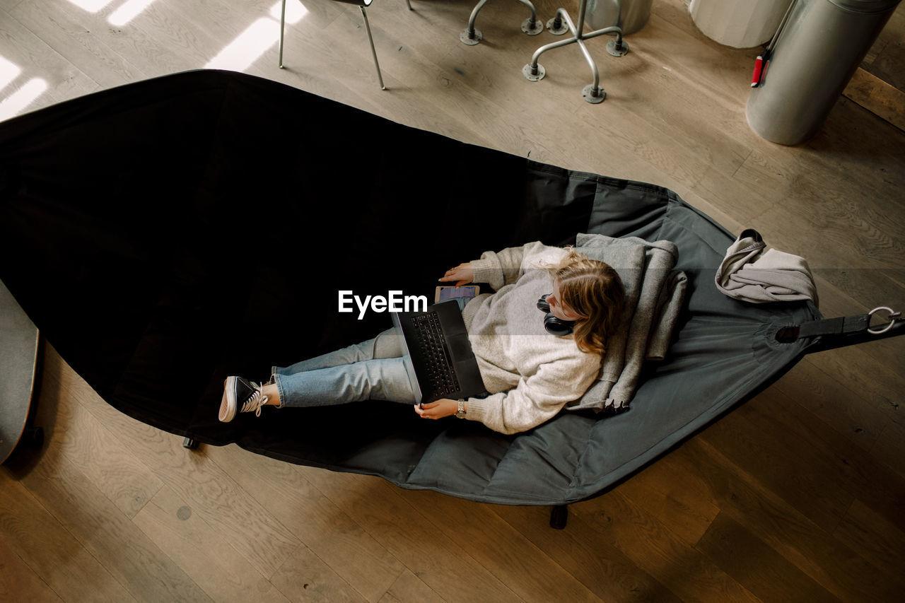 HIGH ANGLE VIEW OF MAN SLEEPING ON HARDWOOD FLOOR