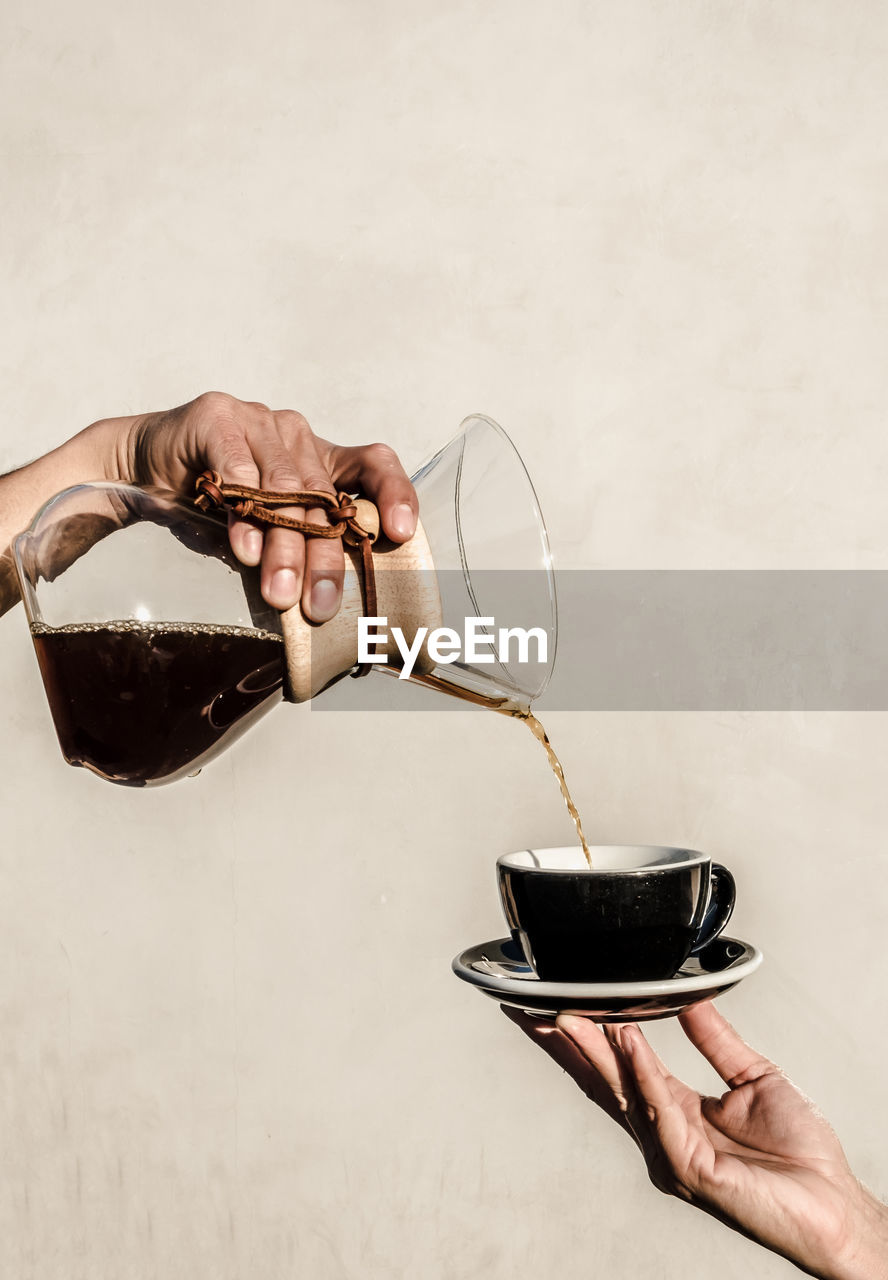 holding, human hand, human body part, hand, refreshment, one person, real people, drink, pouring, food and drink, indoors, cup, mug, body part, container, lifestyles, wall - building feature, household equipment, hot drink, glass, tea cup, finger, human limb