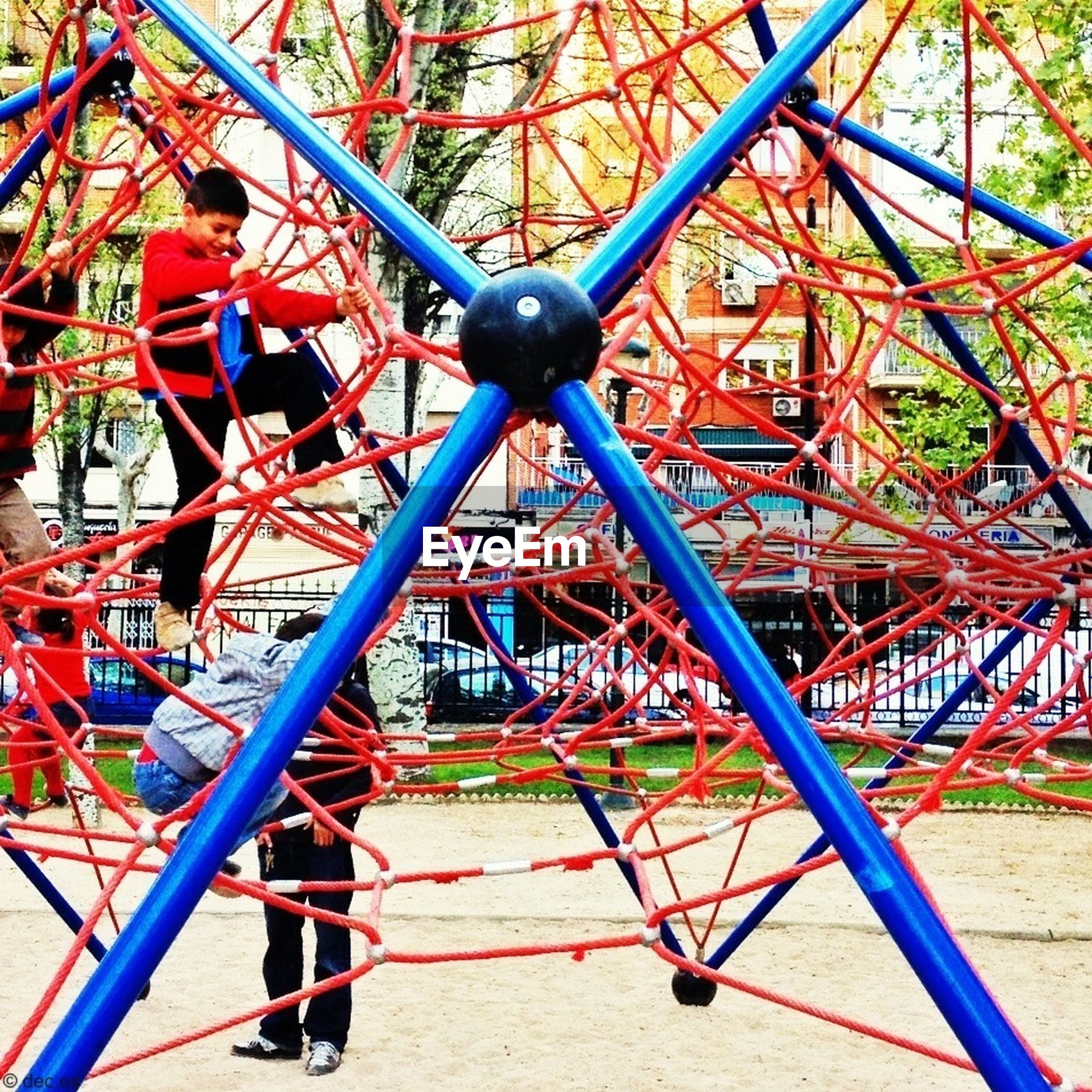 tree, leisure activity, lifestyles, metal, red, playground, childhood, transportation, park - man made space, amusement park, travel, day, bicycle, railing, metallic, casual clothing, mode of transport, sunlight