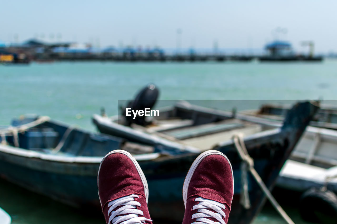 Low Section Of Person Wearing Shoes Against Boats In Lake