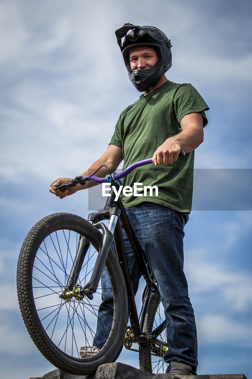 Low Angle View Of Man With Bmx Cycle Standing On Ramp Against Sky