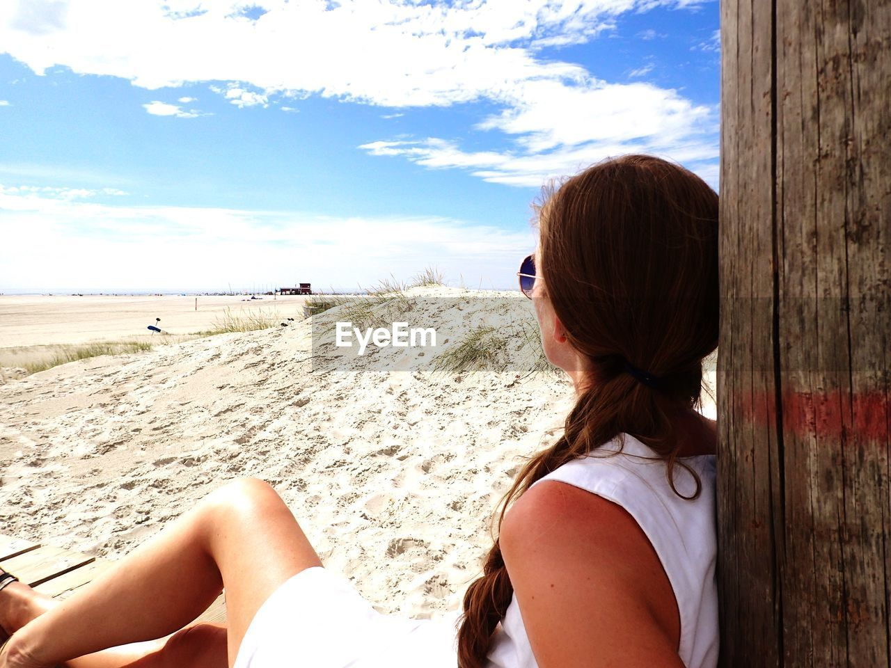 Side view of woman sitting at beach against sky