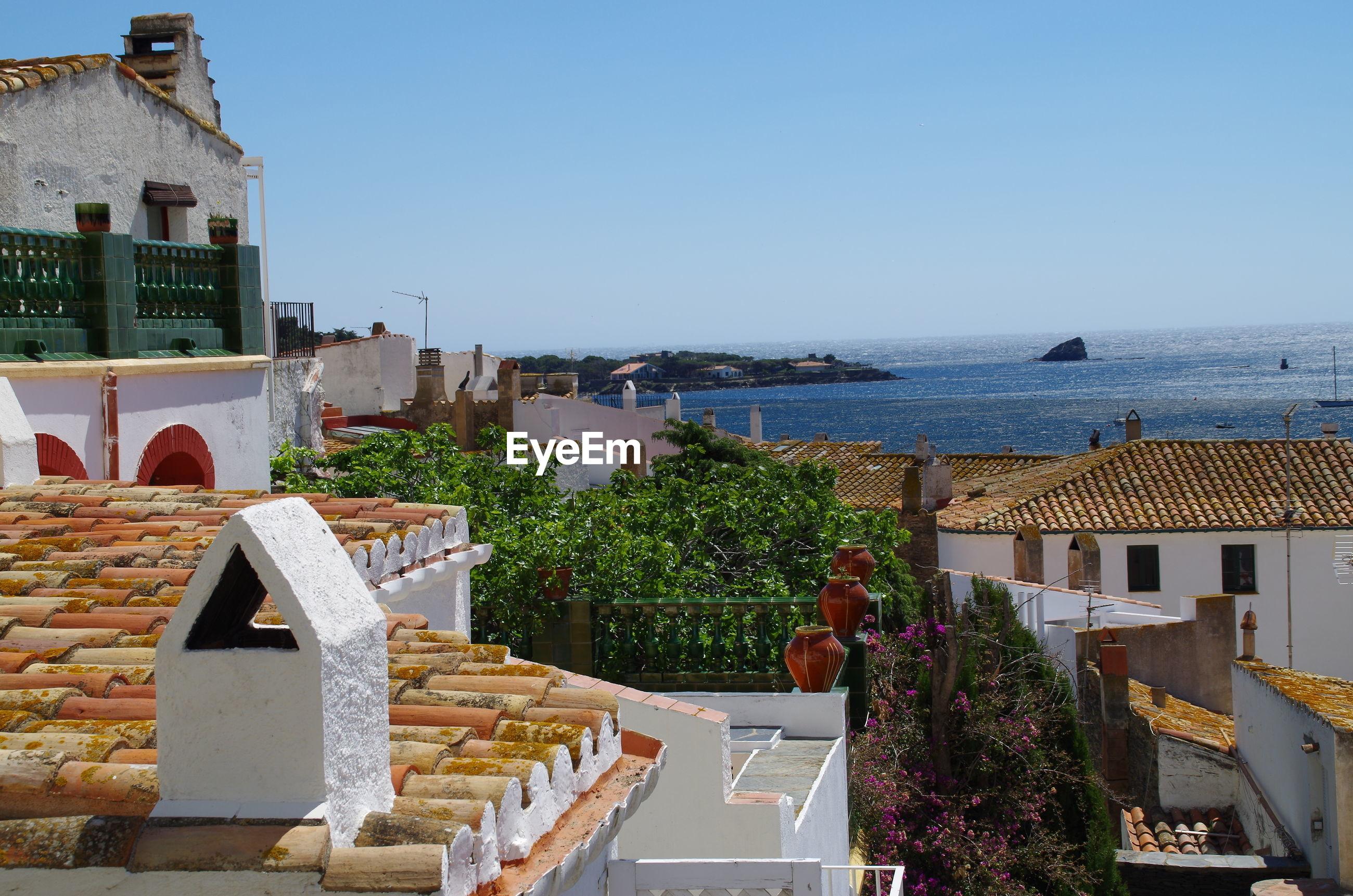 BUILDINGS BY SEA AGAINST CLEAR SKY