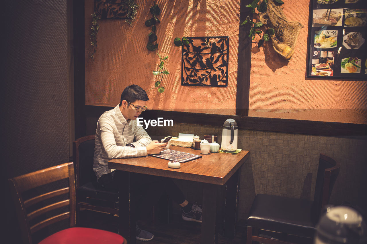 Man Using Mobile Phone While Sitting In Restaurant At Night