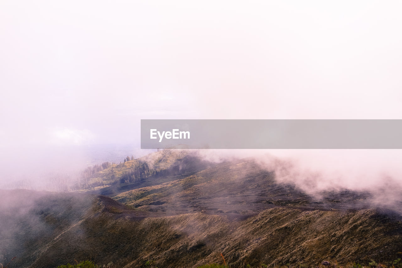 Fog from volcanic mountain against sky