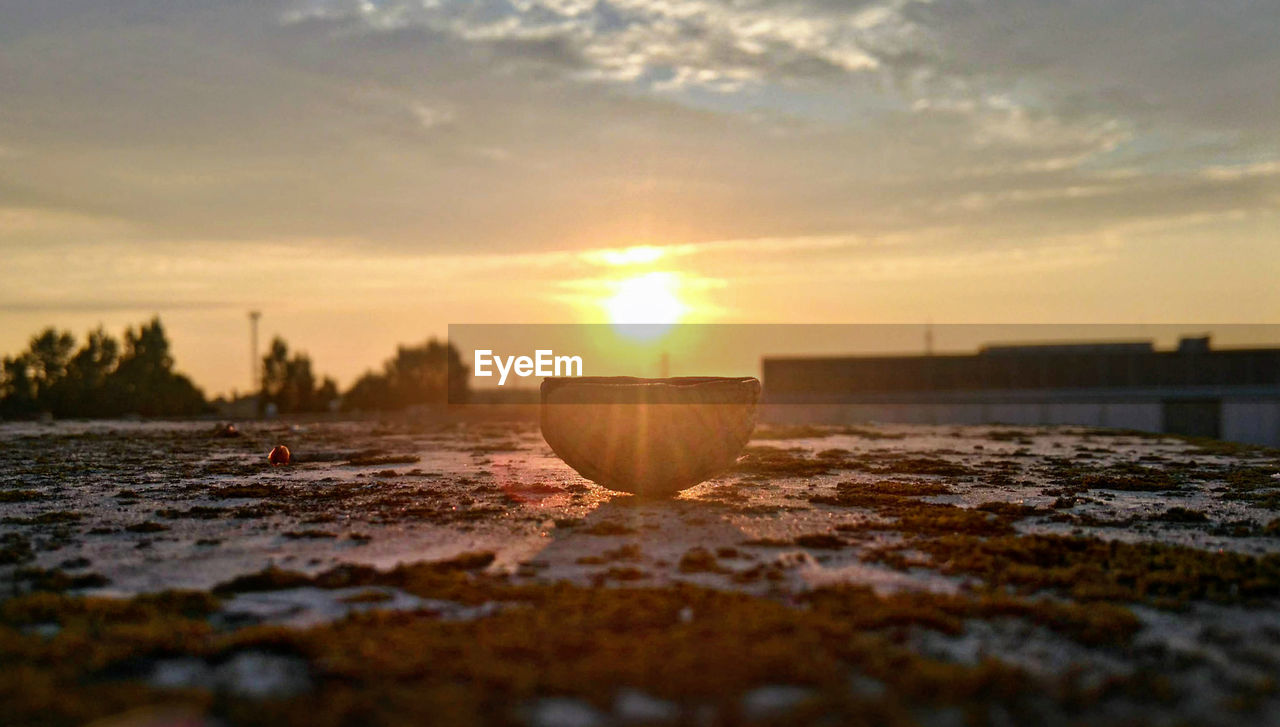 sunset, sky, sun, selective focus, orange color, nature, no people, sunlight, scenics - nature, beauty in nature, land, tranquility, cloud - sky, water, lens flare, tranquil scene, beach, surface level, outdoors, close-up