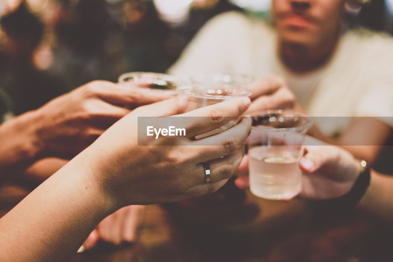 Cropped Hands Of Friends Toasting Drinks In Restaurant