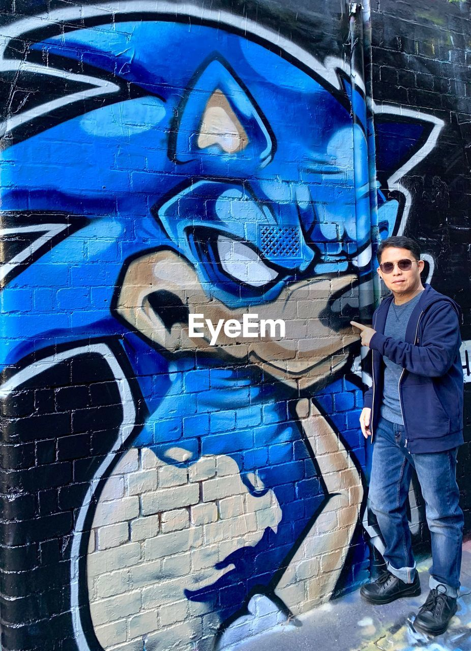 one person, graffiti, blue, art and craft, standing, creativity, wall - building feature, young adult, street art, full length, real people, casual clothing, young men, lifestyles, representation, day, paint, multi colored, mural