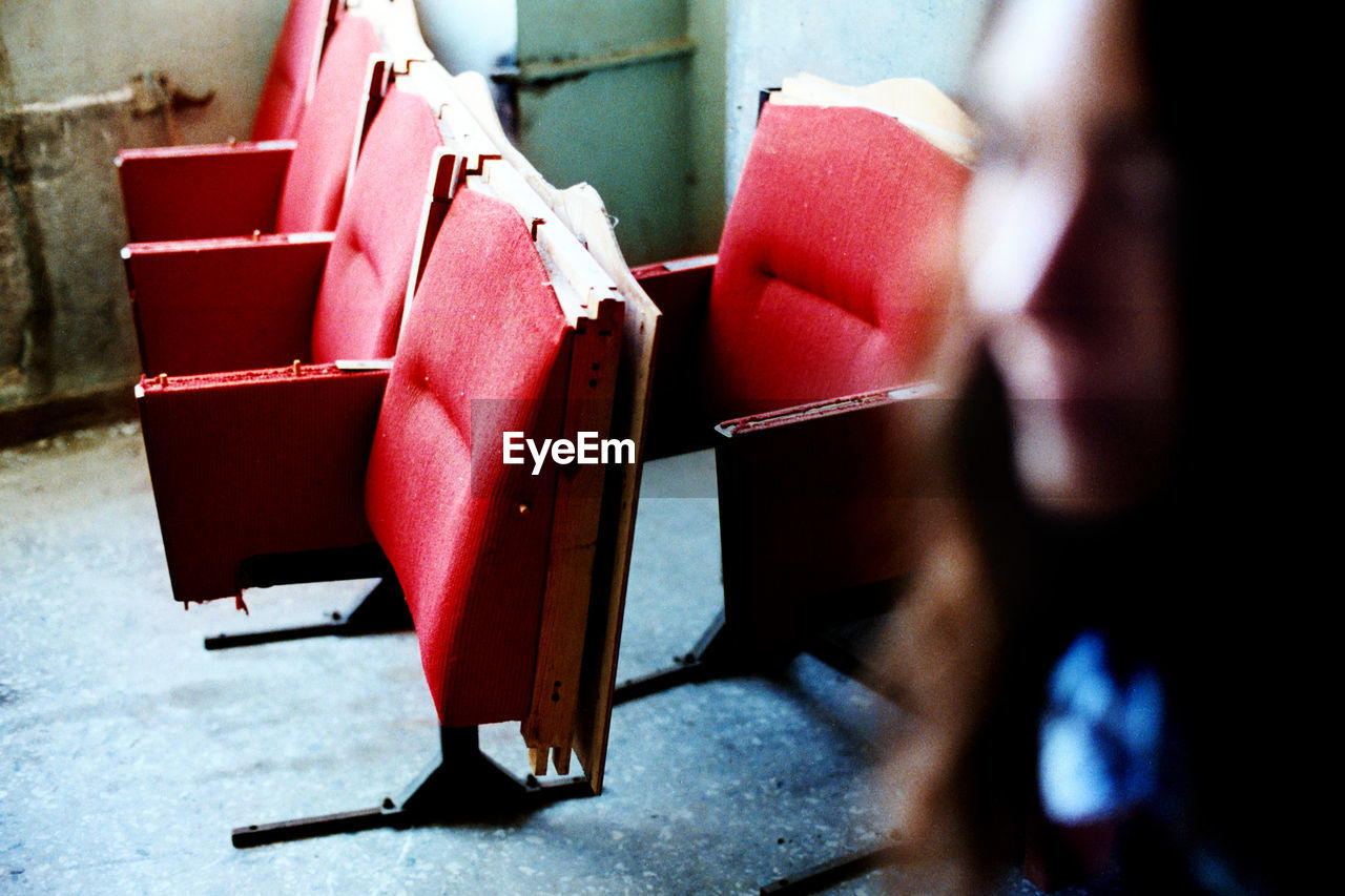 Cropped Image Of Woman With Broken Red Seats At Theater