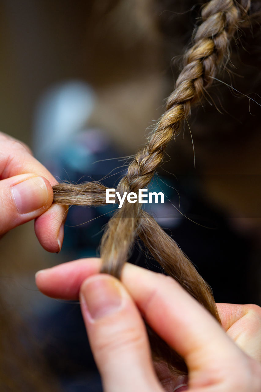 Cropped Hands Of Woman Braiding Hair
