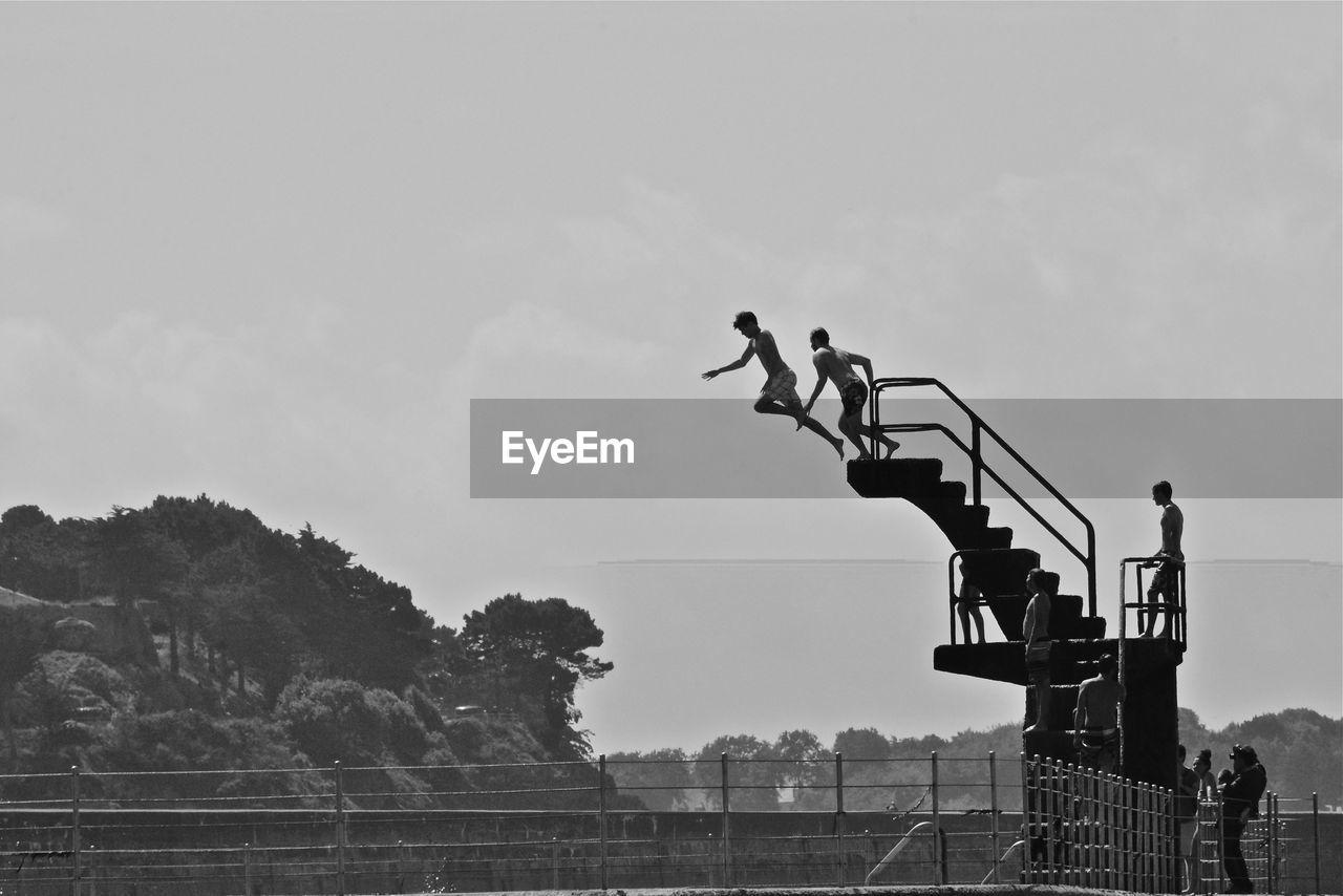 Men diving from platform against sky