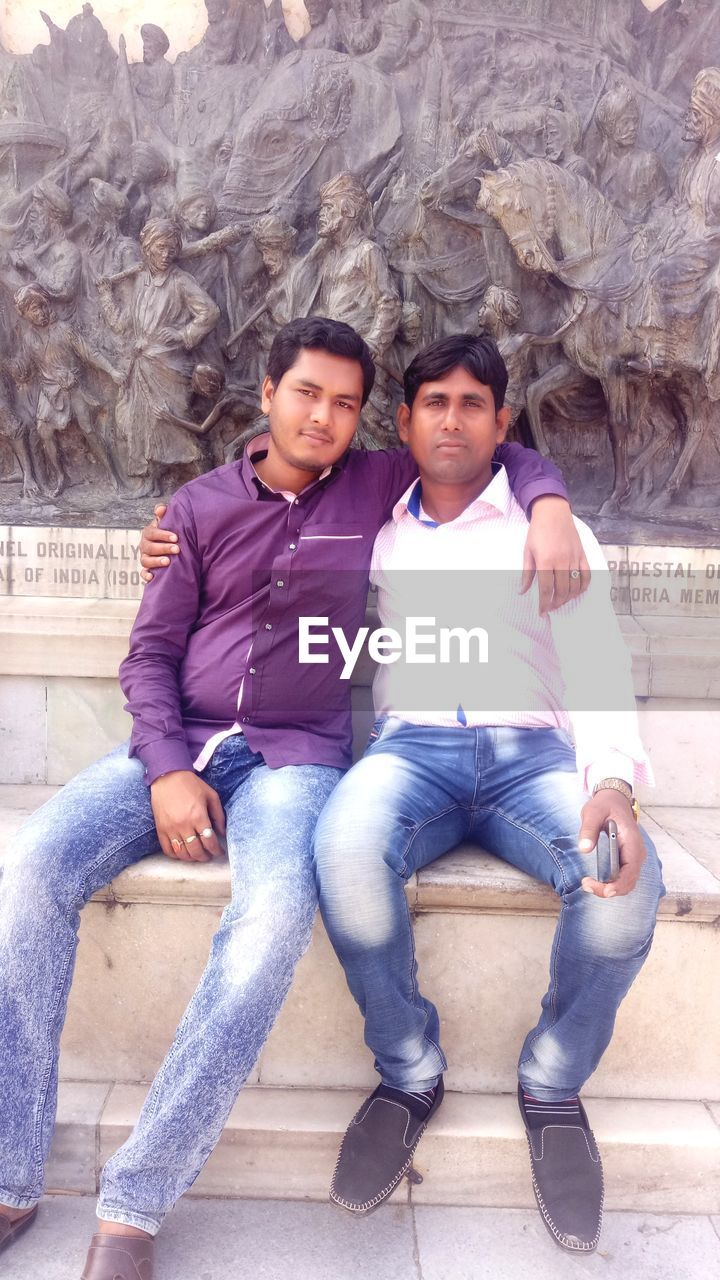 young men, two people, full length, front view, sitting, young adult, young women, real people, casual clothing, togetherness, looking at camera, portrait, love, lifestyles, leisure activity, happiness, day, smiling, young couple, outdoors, bonding