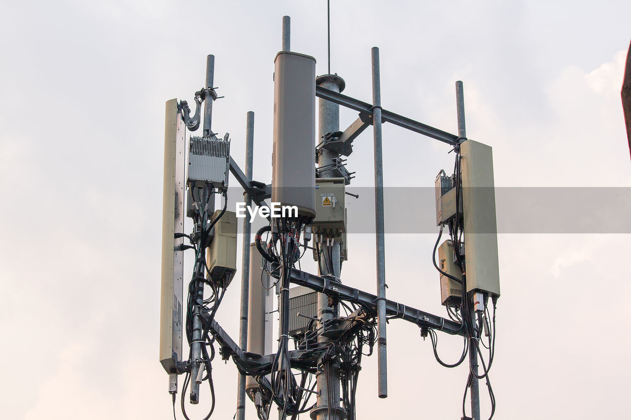 sky, technology, low angle view, no people, lighting equipment, safety, security, nature, cloud - sky, security camera, fuel and power generation, outdoors, connection, metal, protection, day, surveillance, built structure, communication, architecture, electrical equipment