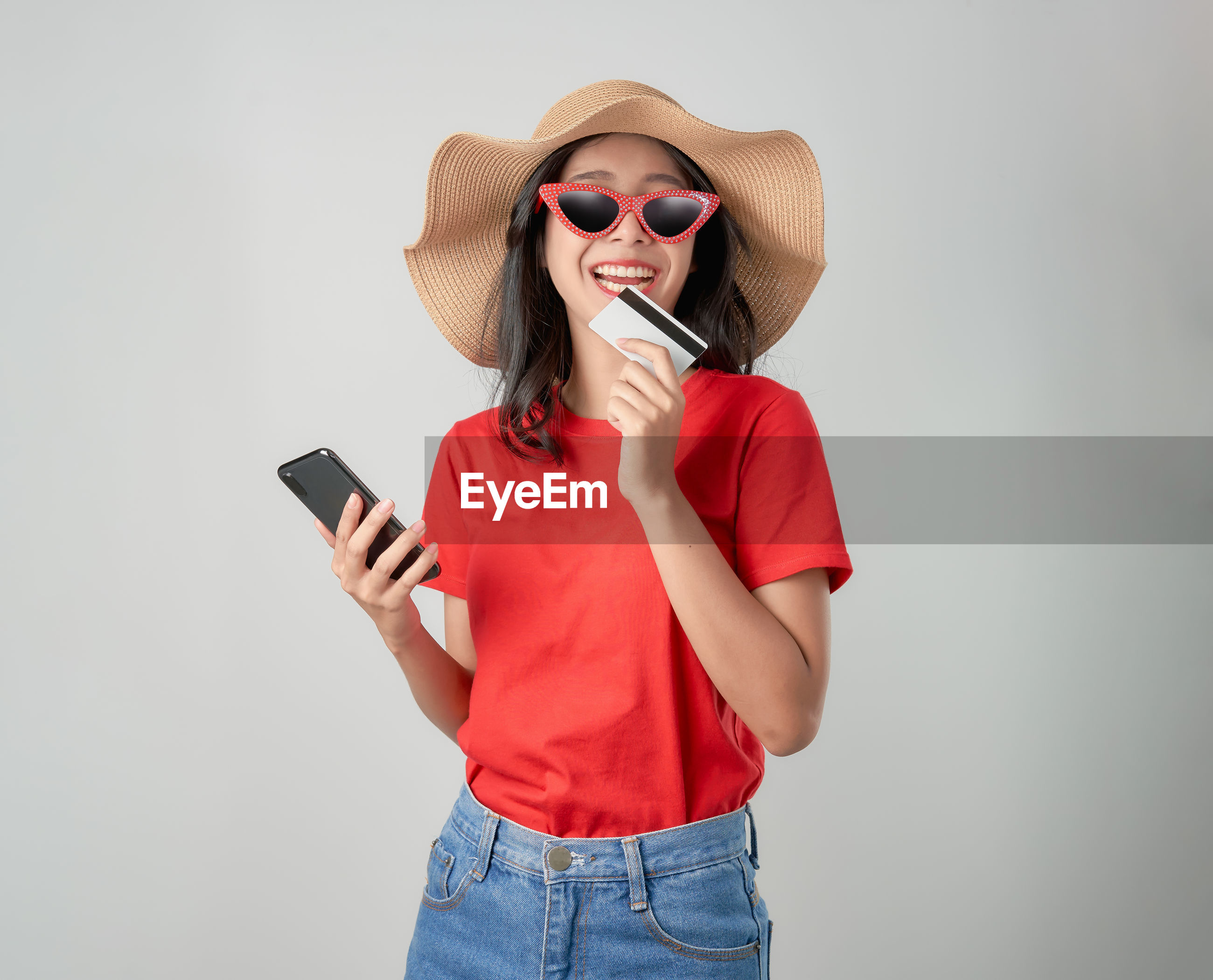 Portrait of young woman holding credit card while using phone against gray background