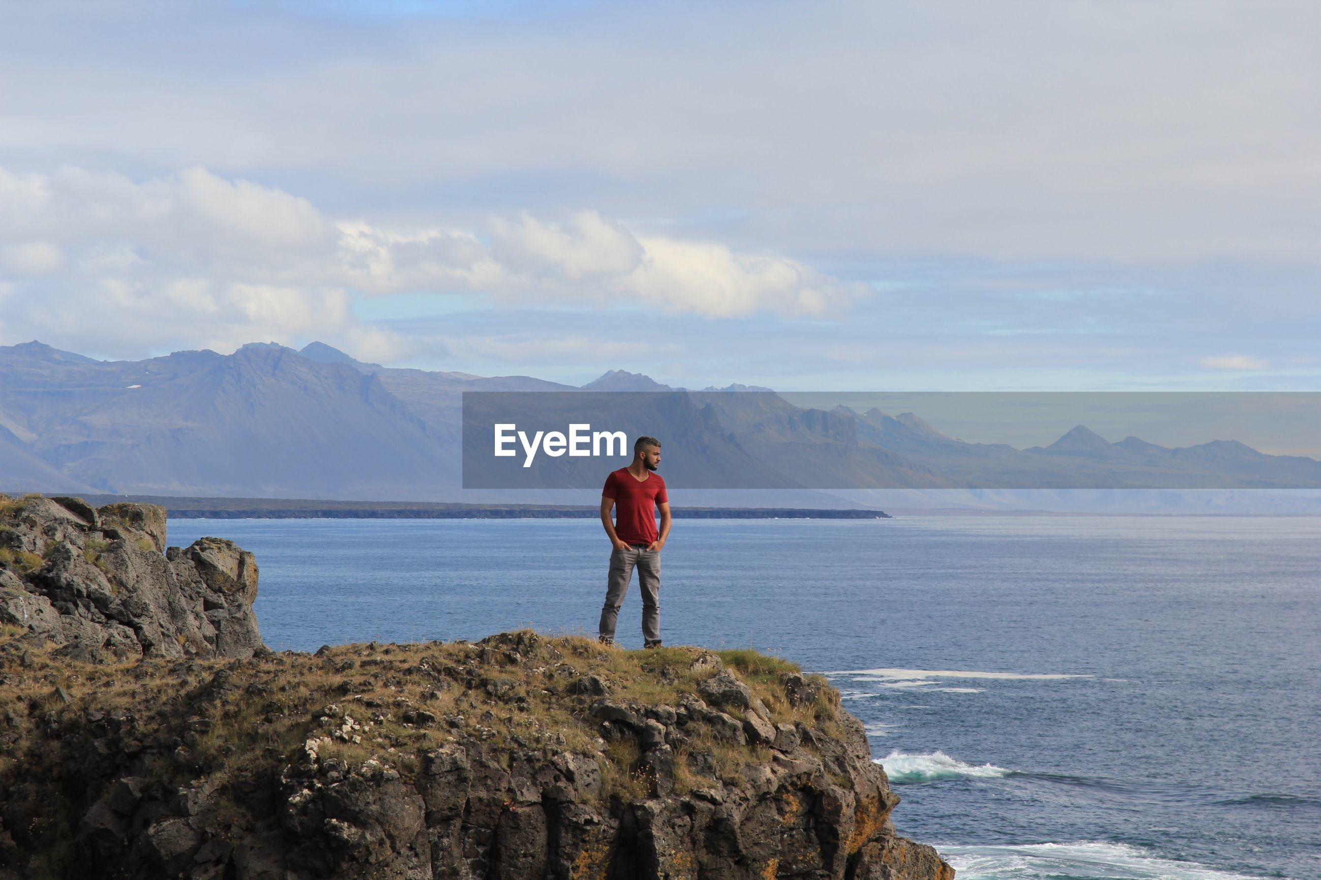 Man looking at sea while standing on mountain against sky