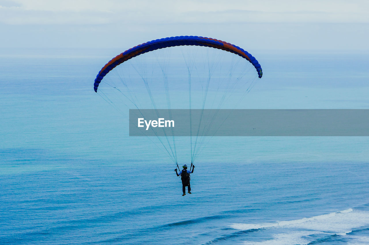 Man paragliding over sea against sky