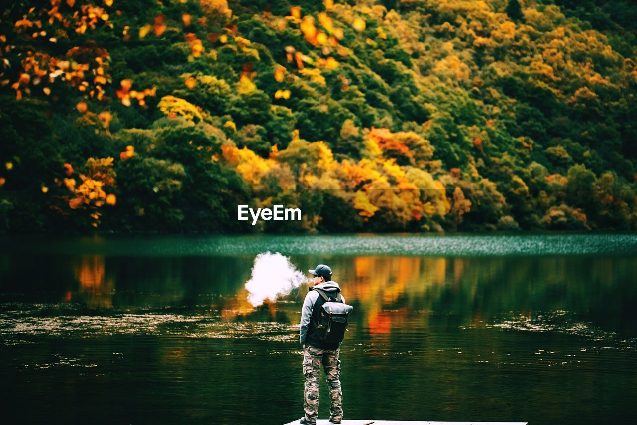 Man exhaling smoke while standing on pier by lake during autumn
