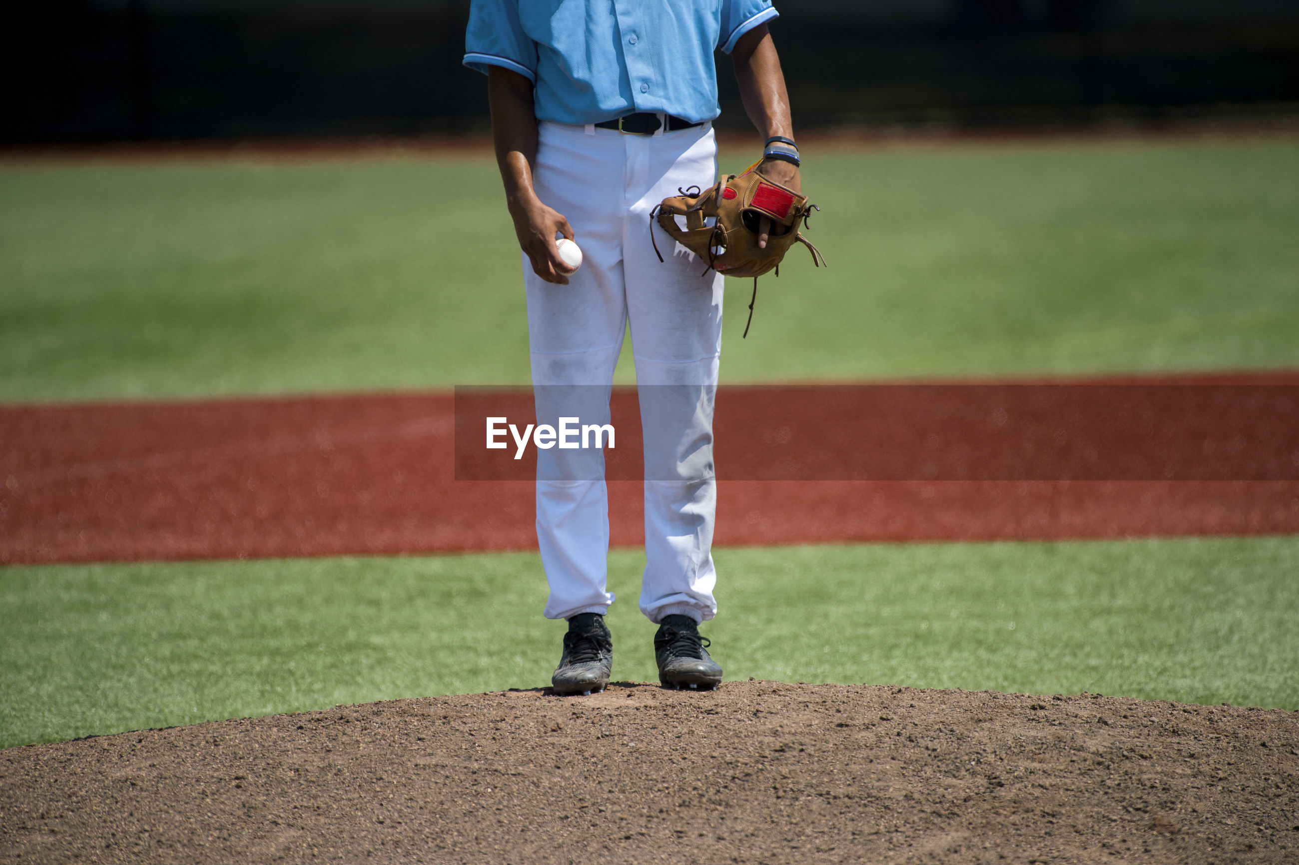Low section of baseball player standing on playing field during sunny day