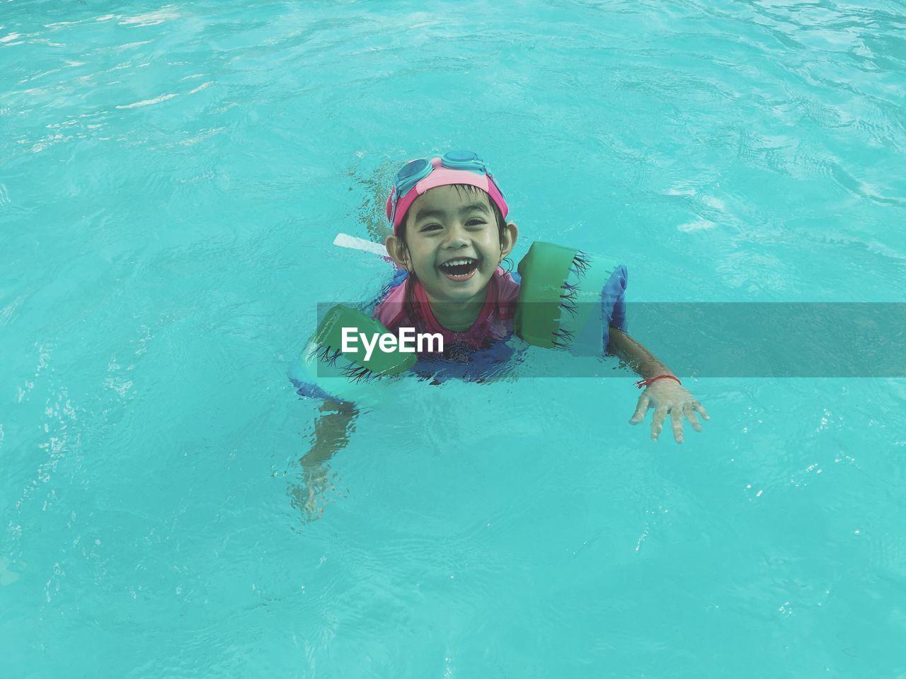 Portrait of cute girl in swimming pool
