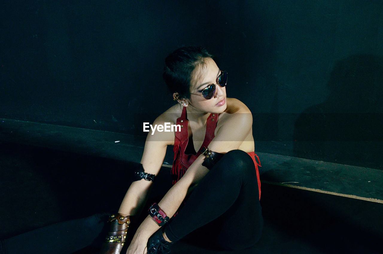 High angle view of young woman looking away while sitting against black wall