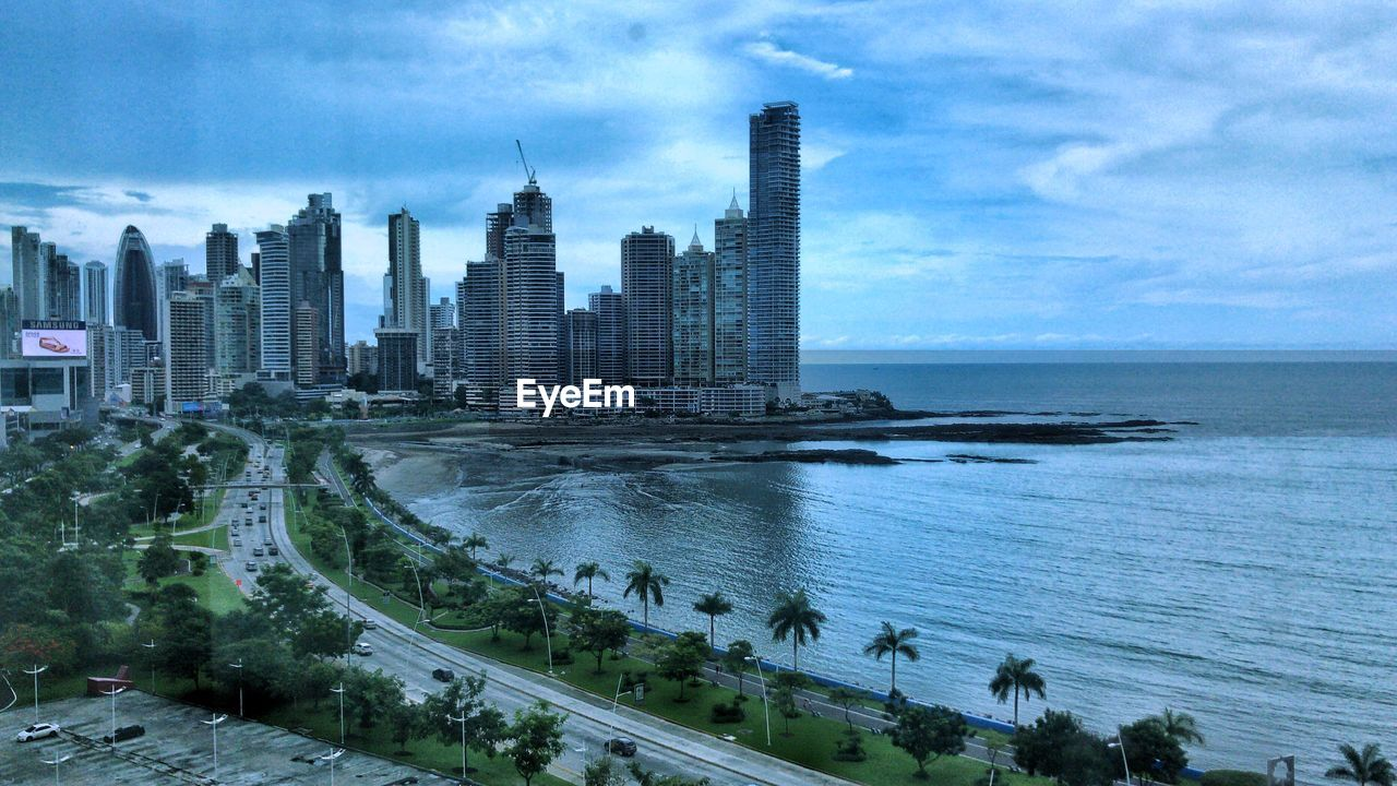built structure, sky, architecture, building exterior, water, city, cloud - sky, building, office building exterior, skyscraper, sea, tower, nature, tall - high, cityscape, day, urban skyline, modern, transportation, no people, outdoors, horizon over water, financial district