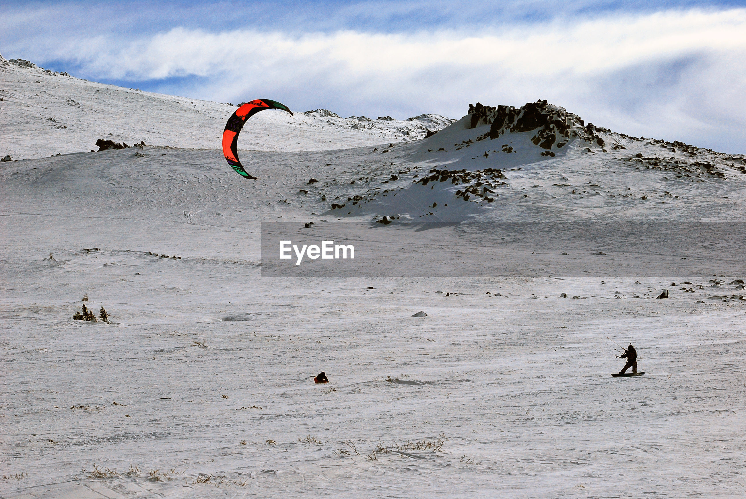 Person kiteboarding at beach against sky