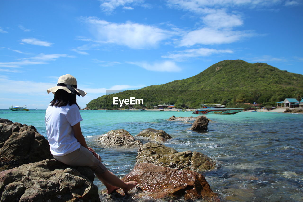 water, rock, rock - object, sky, solid, beauty in nature, scenics - nature, mountain, sea, real people, rear view, nature, lifestyles, hat, leisure activity, cloud - sky, sitting, one person, beach, outdoors, looking at view