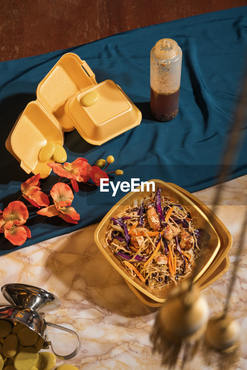 High Angle View Of Noodles In Bowl By Flowers On Table