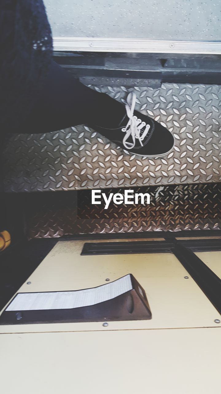 shoe, human leg, human body part, low section, one person, body part, high angle view, indoors, standing, real people, high heels, flooring, women, human foot, day, adult, lifestyles, black color, tiled floor