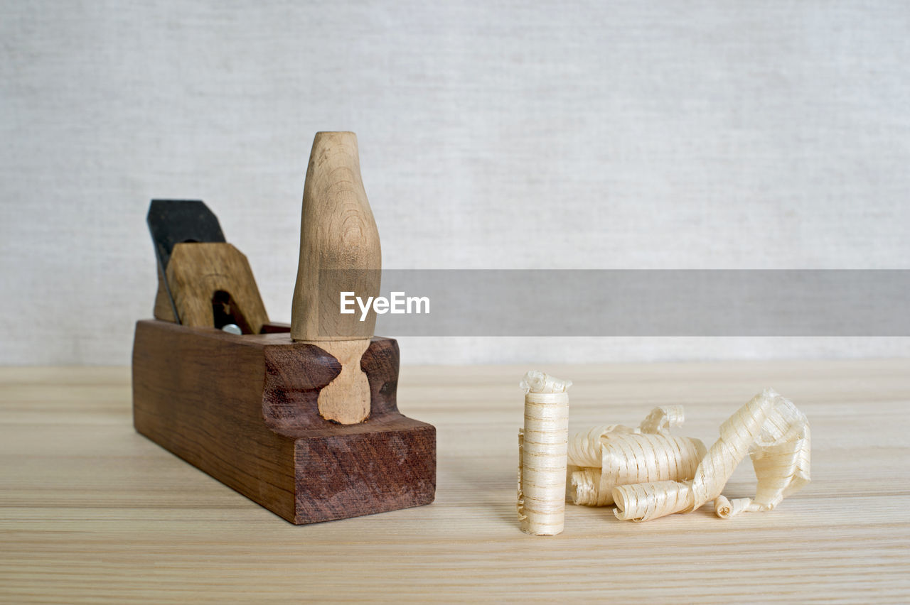 wood - material, still life, indoors, table, no people, close-up, cutting board, focus on foreground, brown, figurine, representation, art and craft, day, copy space, toy, group of objects, studio shot, container, high angle view, side by side