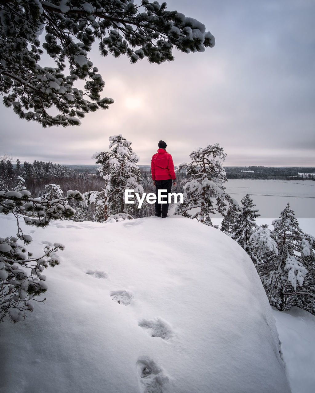 Man standing on snow covered landscape against sky