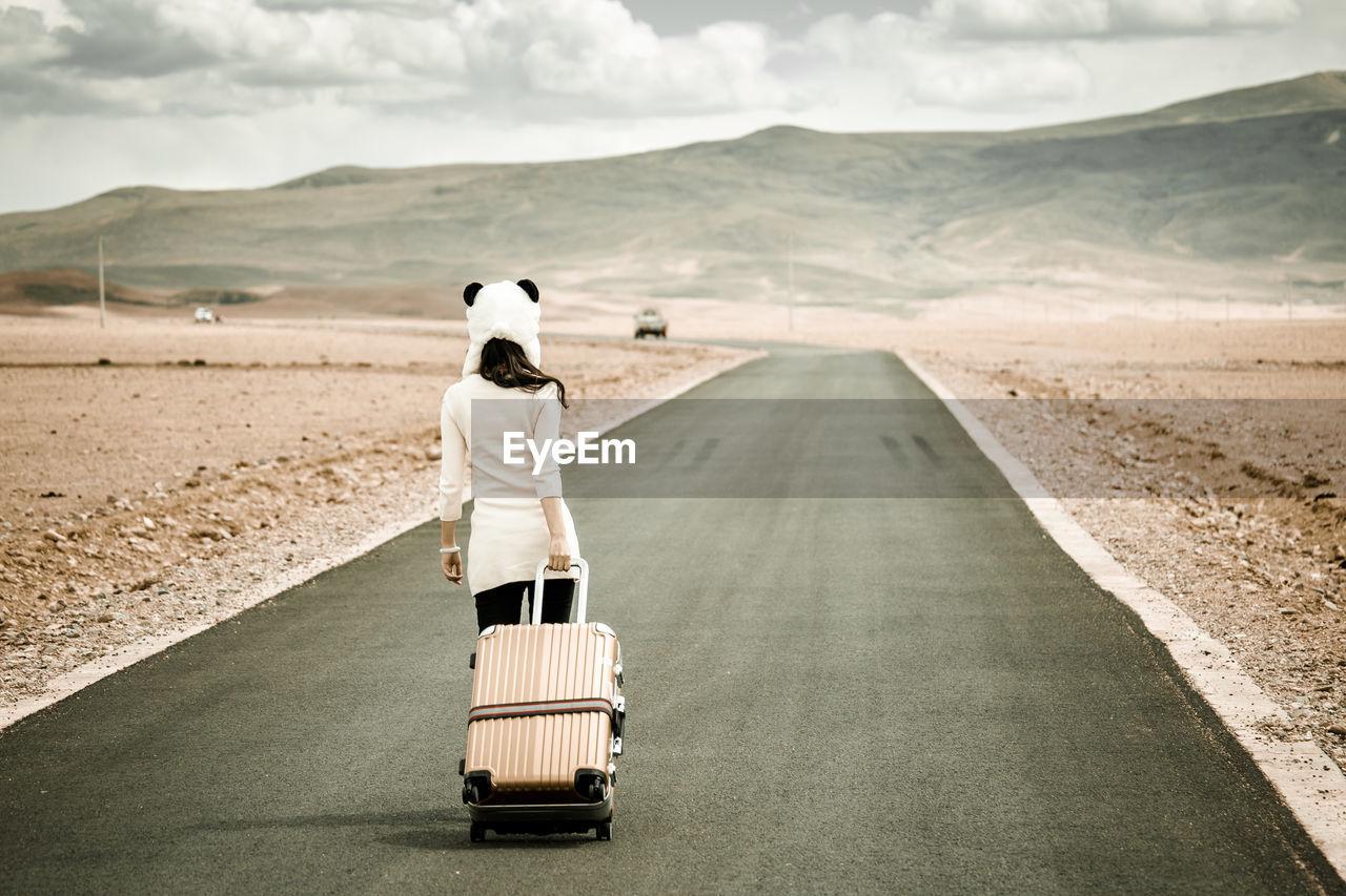 Rear View Of Woman Walking On Road In Desert