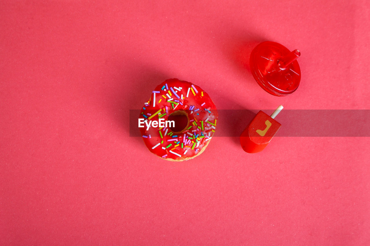 HIGH ANGLE VIEW OF MULTI COLORED CANDIES ON RED BACKGROUND