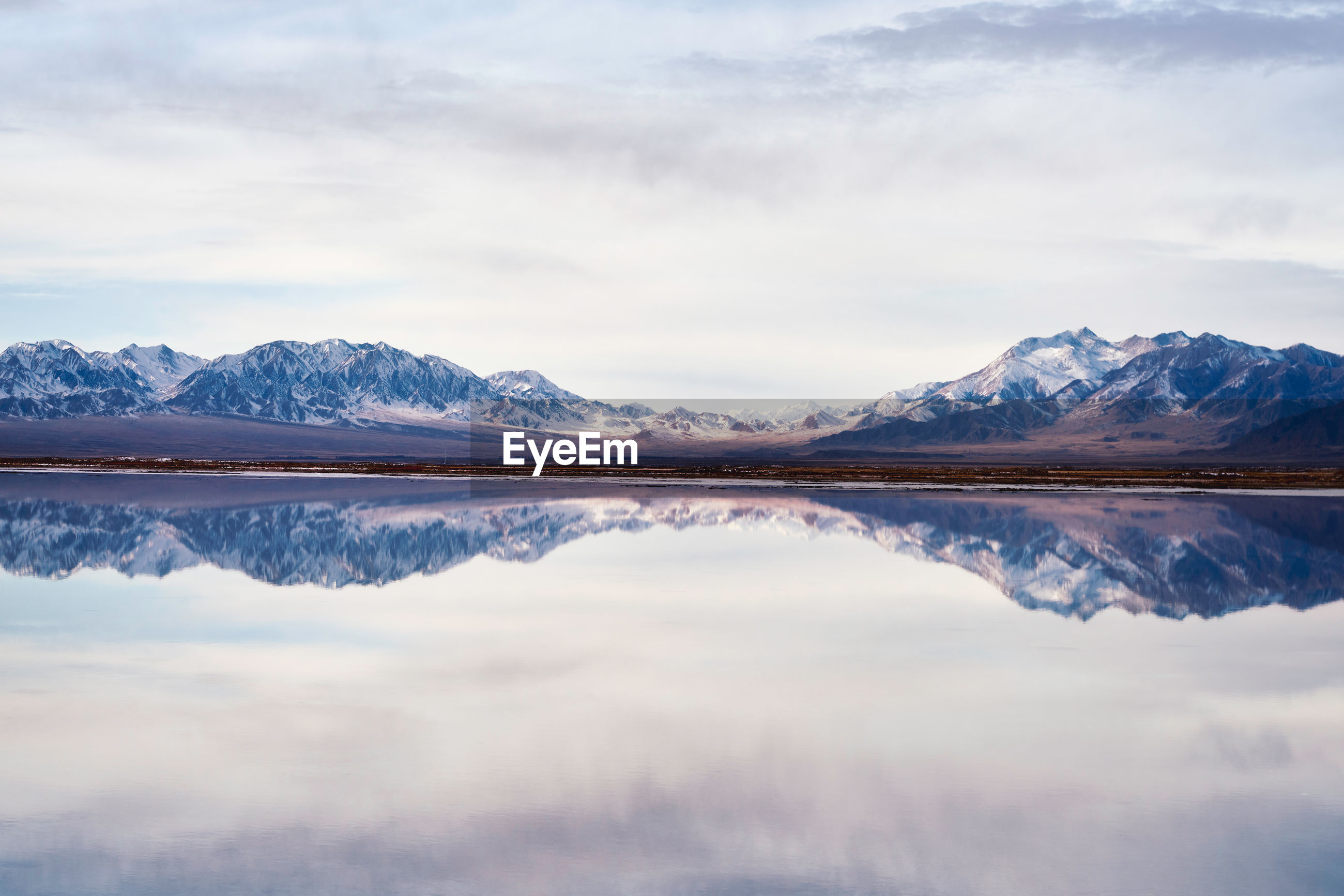 Scenic view of calm lake by snowcapped mountains against cloudy sky