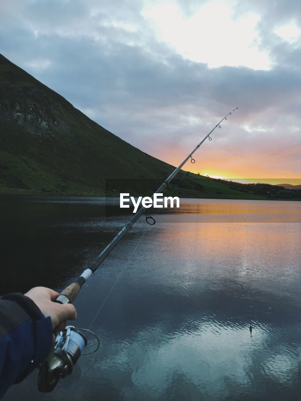 Cropped hand of man fishing in lake against sky