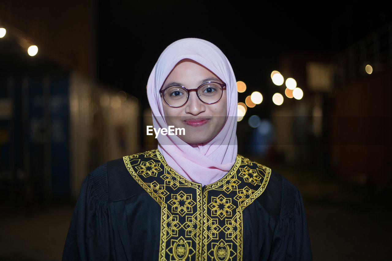 Smiling Young Woman Wearing Mortar Board While Standing Against Sky At Night