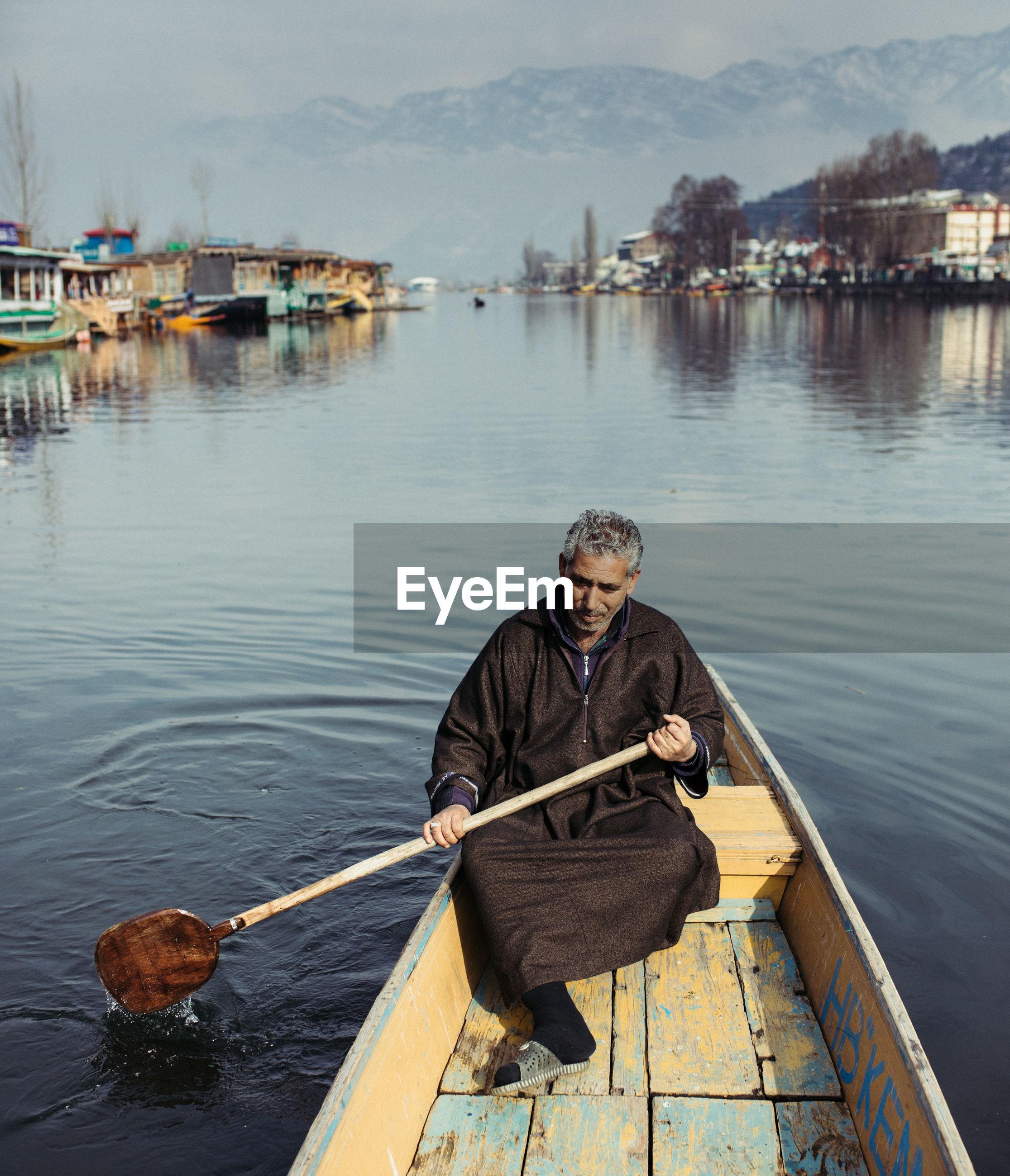 PORTRAIT OF MAN FISHING ON LAKE