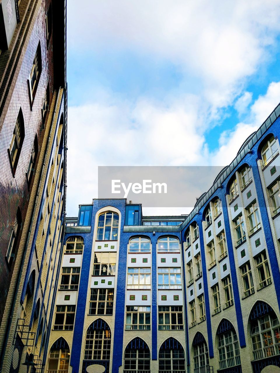 built structure, building exterior, architecture, sky, cloud - sky, building, low angle view, no people, city, window, day, nature, arch, outdoors, residential district, glass - material, sunlight, blue, in a row, office building exterior